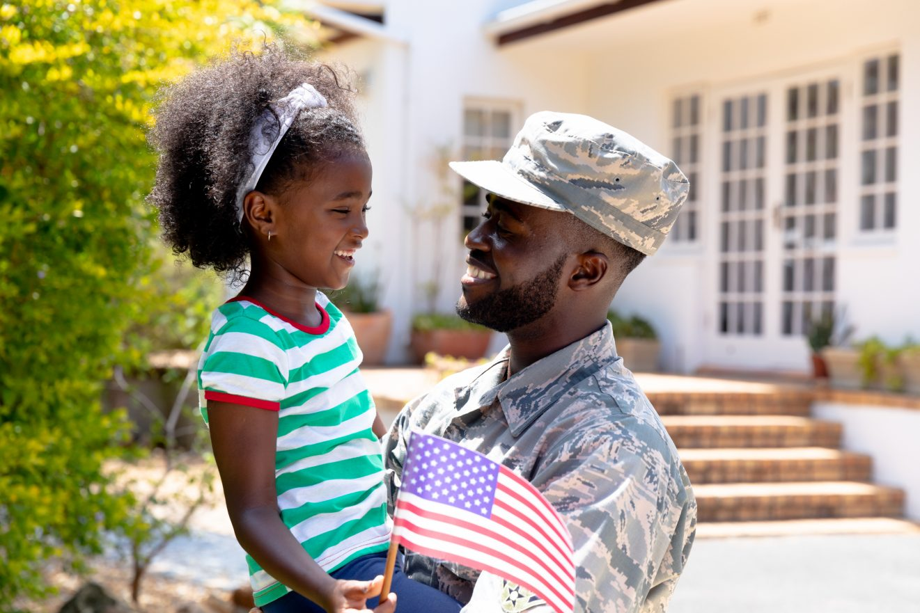 African American male solider wearing uniform holding his daughter with a USA flag in his arms, standing by the house on a sunny day, smiling and interacting.